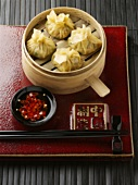 Dim sum in bamboo steamer with chilli dip