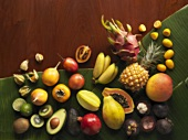 Whole and halved exotic fruit on banana leaves