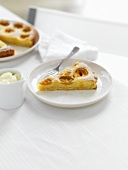 Piece of apricot almond tart with whipped cream, tart in background