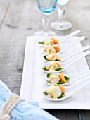 Spiny lobster with papaya on china spoons
