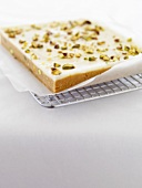 Lime and pistachio slice on a cake rack