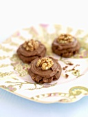 Three chocolate walnut biscuits on a plate