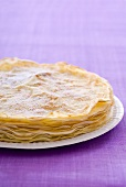 Several sugared crêpes on a plate