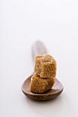 Two brown sugar cubes, one on top of the other, on wooden spoon