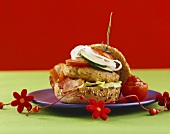 Wholemeal burger with bacon, cucumber, onion and tomato