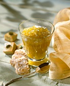 A glass of orange and fig jam with biscuits