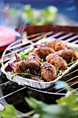 Cevapcici with herbs in an aluminium dish on a barbecue