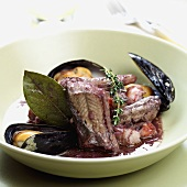 Eel in red wine with mussels and herbs