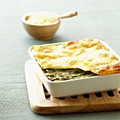 Asparagus lasagne in a baking dish on a trivet