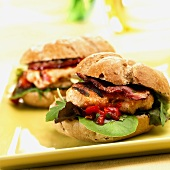 Two chicken burgers with bacon and barbecue sauce