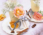 Place-settings with roses, gypsophila and Christmas spices
