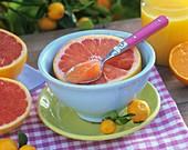 Half a grapefruit in a bowl and orange juice