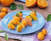 Zwei Fruchtspiesse mit Kumquat, Orange, Grapefruit und Minze