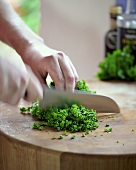 Man chopping curly parsley on wooden surface