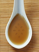 Sesame oil in a china spoon on a bamboo mat