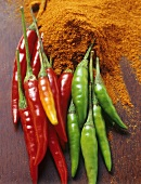 Fresh chillies and chilli powder on wooden background