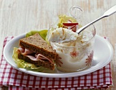 Horseradish mousse in a jar with ham sandwich