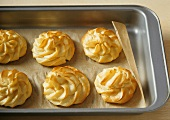Six profiteroles on baking tray lined with baking parchment