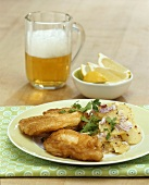 Carp fillet in beer batter with potato salad, glass of beer
