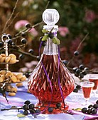 Sloe gin in decanter and glasses with sloes out of doors