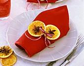 Serviettendekoration mit getrockneten Orangenscheiben, Sternanis