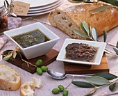 Basil- & tomato pesto in small dishes with olives, ciabatta