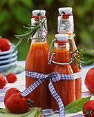 Tomato juice in 3 flip-top bottles, tomatoes, rosemary, bay