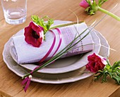 Place-setting with poppy anemone and bear grass on napkin