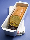 Banana cake, slices removed, in a terrine dish