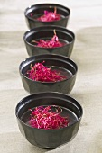 Chicken soup with beetroot sprouts in four bowls