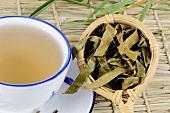 Getrocknete Wollmispelblätter in Teesieb mit einer Tasse Tee