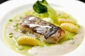 Fried sea bass with peas, pak choi and gnocchi