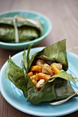 Chicken and pumpkin baked in a banana leaf