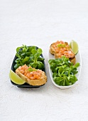 Salmon tartare on baguette with corn salad and lime