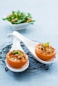 Baked, stuffed tomatoes on china spoons