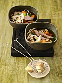 Vegetable noodle soup with veal fillet in two bowls