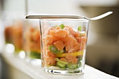 Salmon tartare with coriander on spring onions in glasses