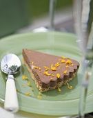 A piece of orange chocolate cheesecake with biscuit base