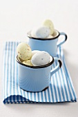 Coloured quails' eggs for Easter in two enamel cups