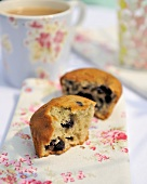 A halved blueberry muffin with tea for breakfast