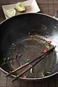 Empty (used) wok with chopsticks