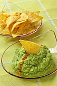 Broccoli dip with tortilla chips in glass dishes