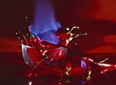 Burning red chillies in and beside a glass dish
