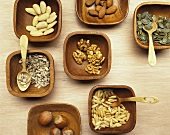 Various nuts in wooden bowls with wooden spoons