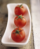 Three cocktail tomatoes in a porcelain dish