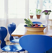 Table with a bowl of fruit and blue chairs