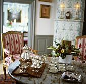 Tray, silver teaset, cups & saucers & chocolates on table