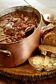 Beetroot soup with beef in a copper pot, slices of bread