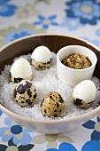 Unshelled and half-shelled quails' eggs on sea salt