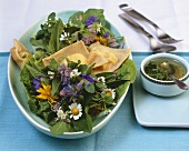 Wild herb salad with pasta squares filled with soft cheese